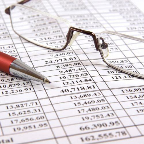 Stift und Gläser auf Finanzbericht